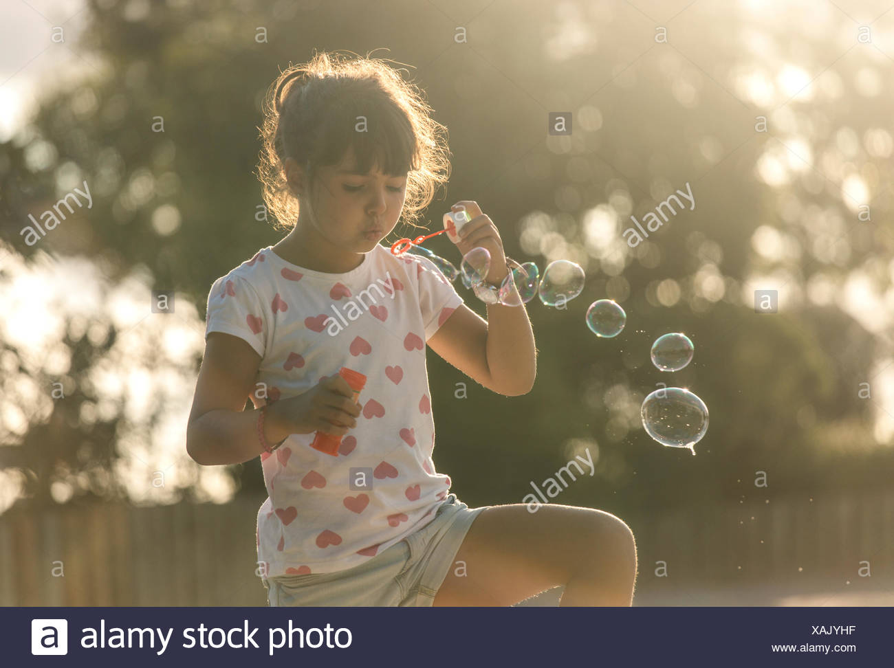 Little girl making soap bubbles in the park at twilight Stock Photo