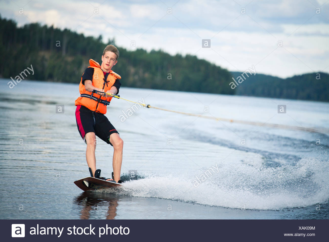 Sweden, Ostergotland, Lake Risten, Teenage boy (14-15) wakeboarding - Stock Image