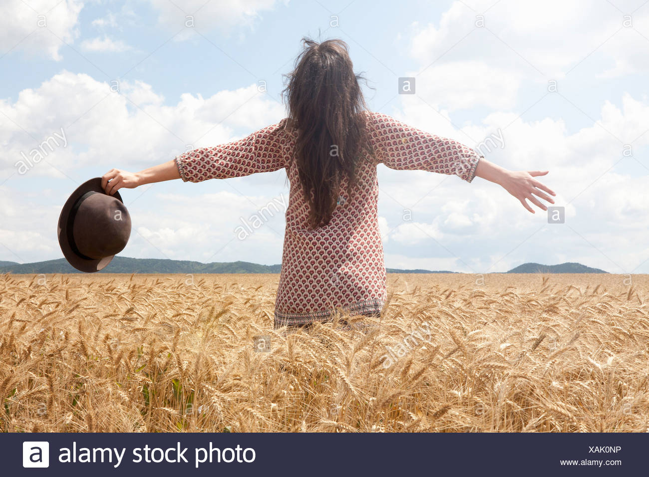 Mid adult woman standing in wheat field with arms out wide - Stock Image
