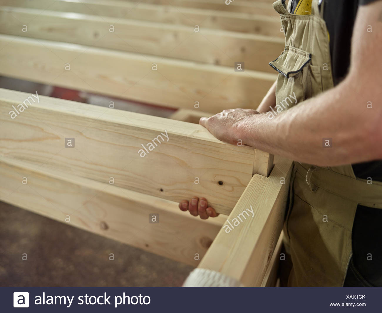 Men's hands connect two wooden beams with tongue and groove Connection of a wooden construction, Austria - Stock Image