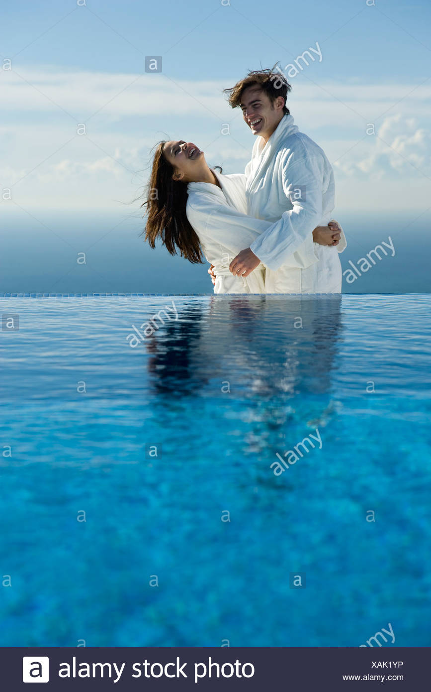 Couple embracing and laughing at edge of infinity pool, both wearing bathrobes - Stock Image