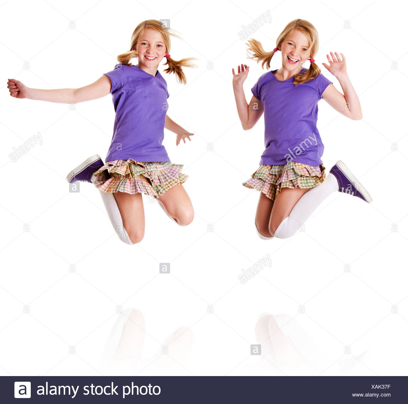 Happy teenager girls identical twins jumping and laughing of happiness having fun, isolated. - Stock Image