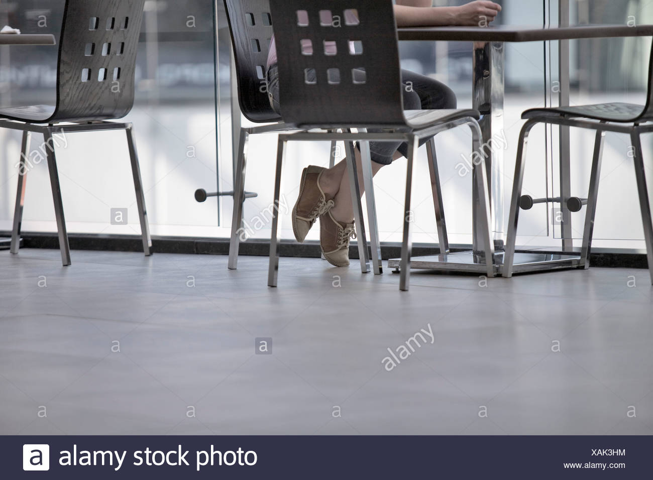 detail of young woman sitting in canteen - Stock Image