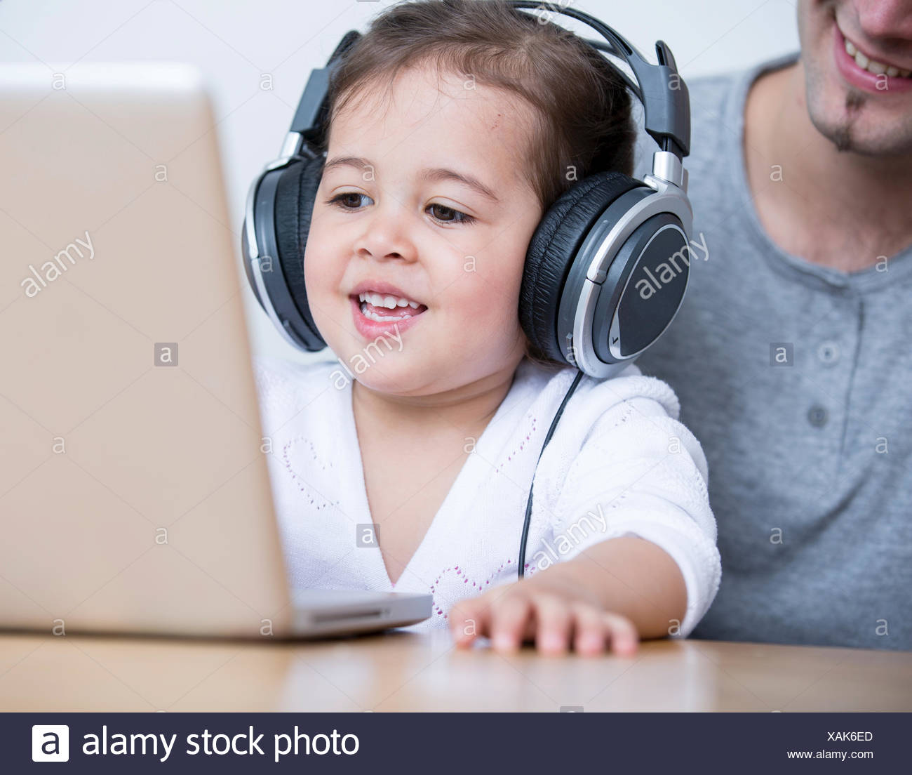 Little girl wearing headphones while looking at laptop with father at table in house - Stock Image