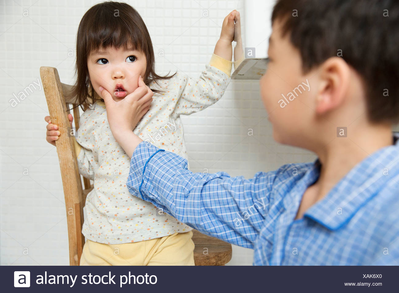 Mischievous brother holding young sisters face - Stock Image