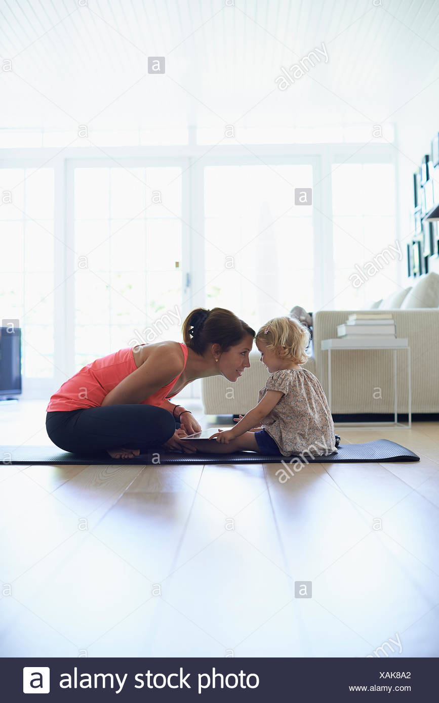 Mid adult mother and toddler daughter practicing lotus position in living room - Stock Image