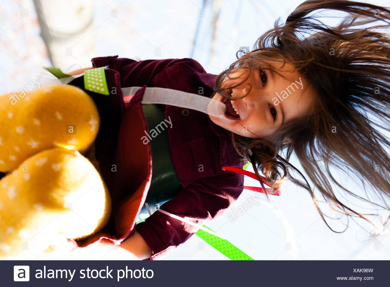 Low angle view of girl wearing colourful tights playing on swing looking at camera smiling - Stock Image