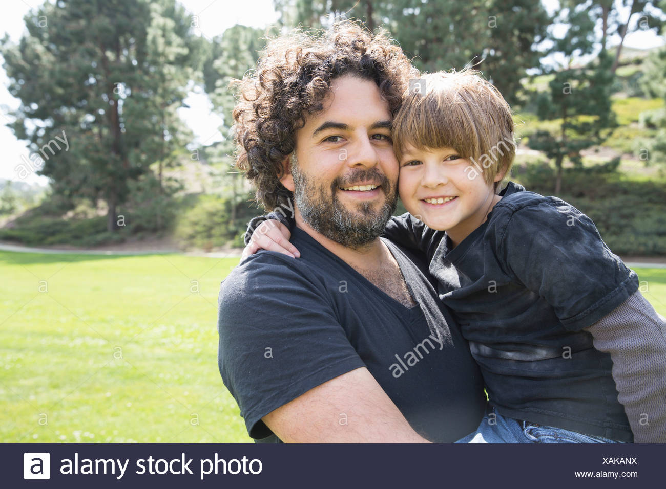 Portrait of proud father and son in park - Stock Image