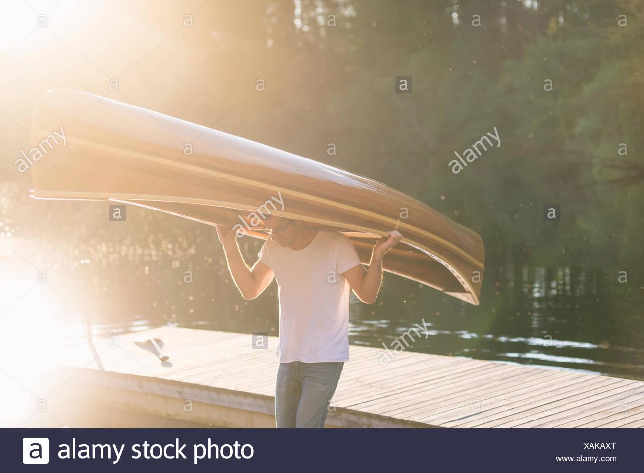 Sweden, Vastmanland, Hallefors, Bergslagen, Man carrying wooden rowboat on head - Stock Image