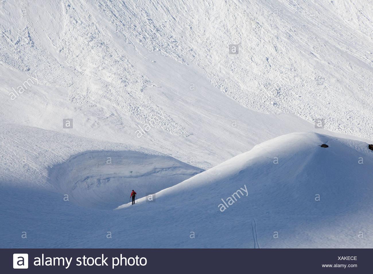 Back-country skier near snowdrift, Canton of Ticino, Switzerland - Stock Image