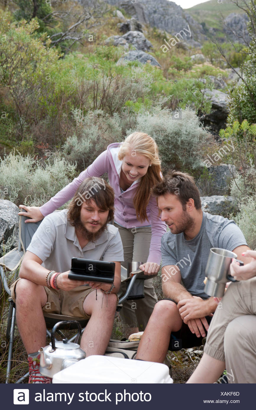 Group of young hikers taking a break, looking at hand held computer - Stock Image