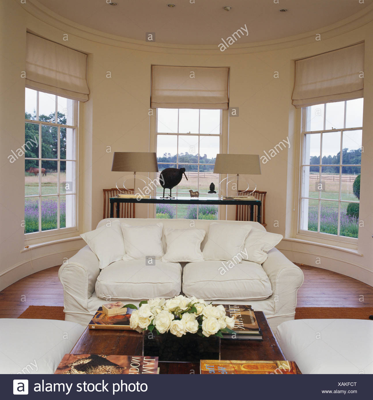 White sofa in front of large bay windows with white blinds in country drawing room - Stock Image