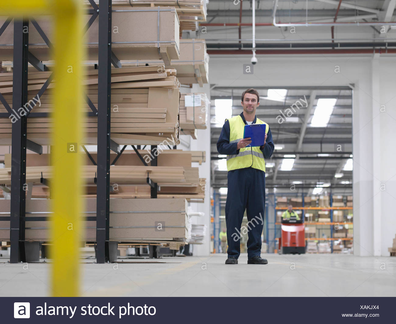 Worker With Clipboard In Warehouse Stock Photo