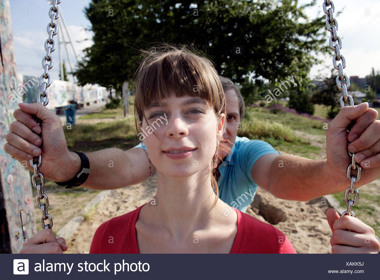 Man pushing woman on playground swing - Stock Image