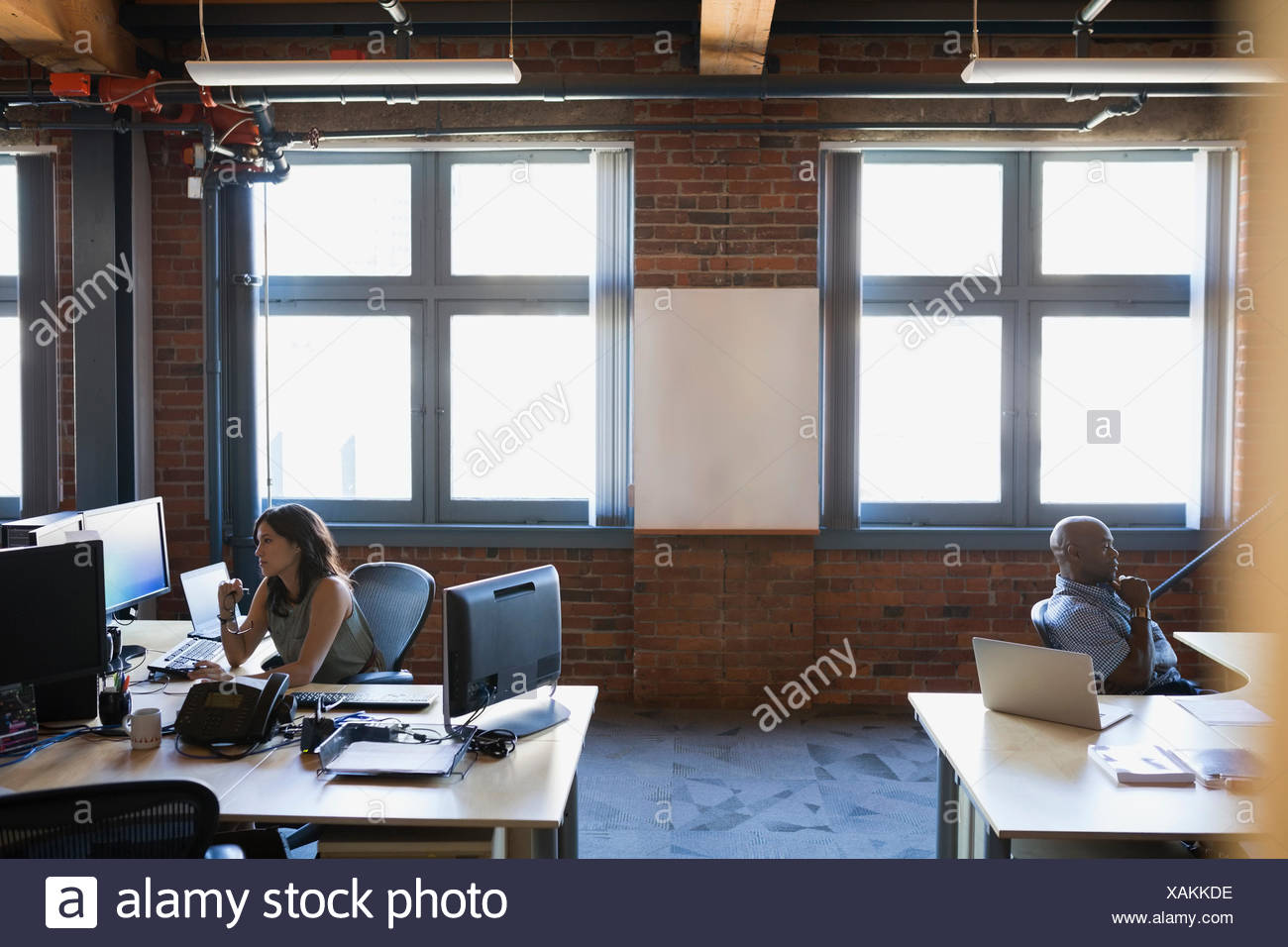 Business people working at desks in office - Stock Image