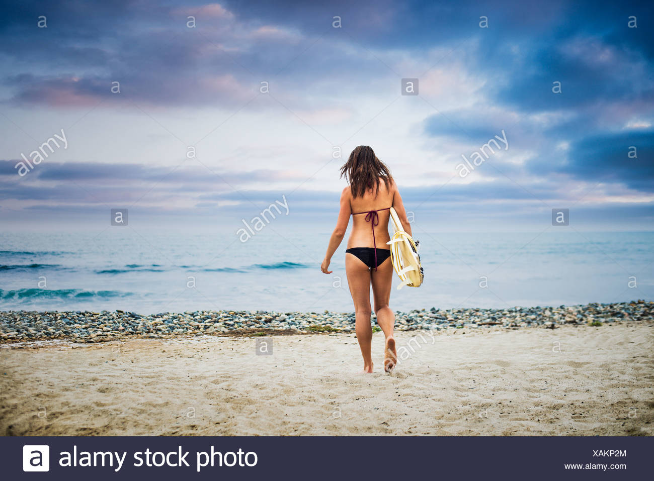 Young woman carrying surfboard to sea - Stock Image