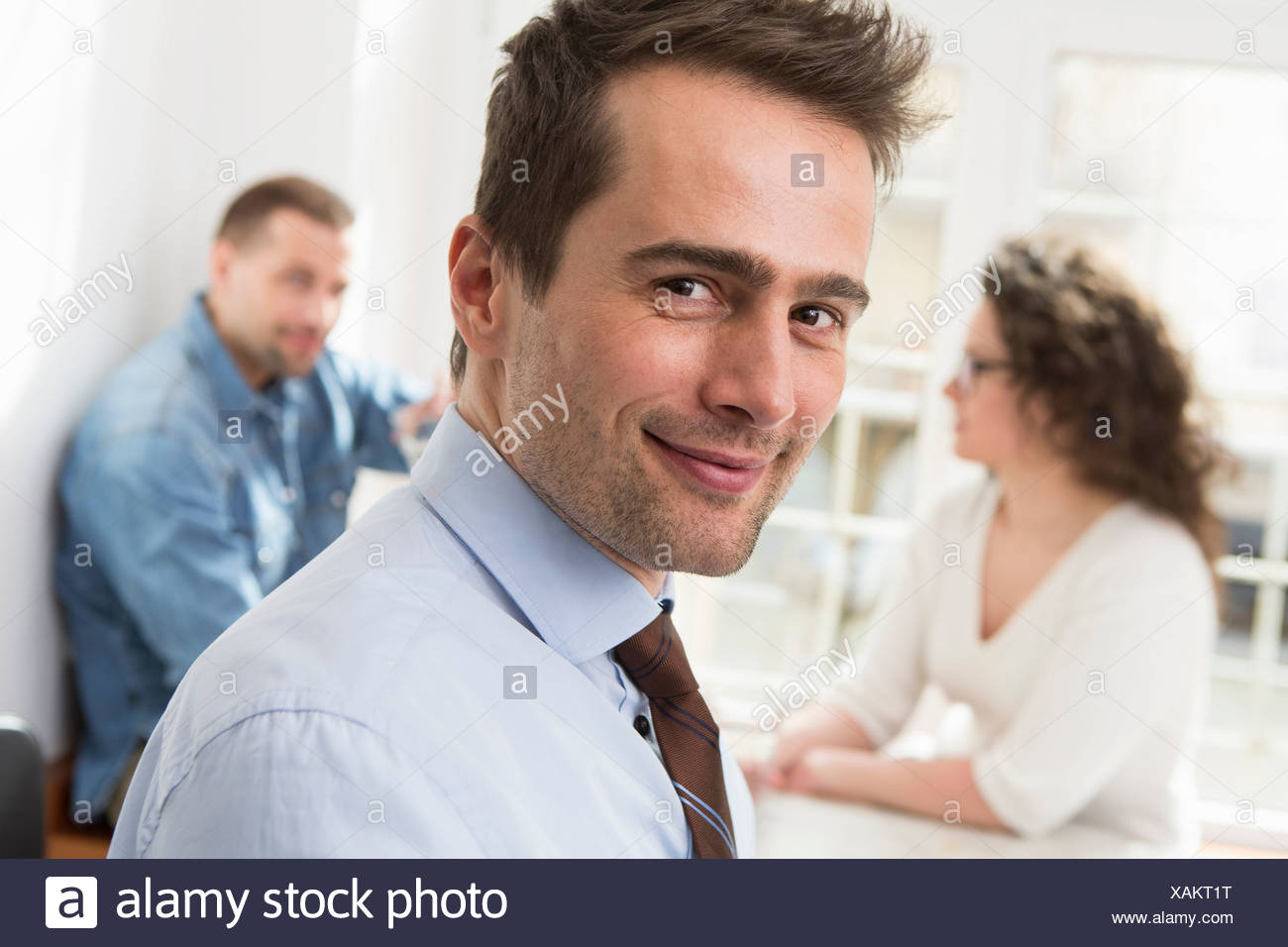 Mature man smiling at camera, mid adults in background - Stock Image