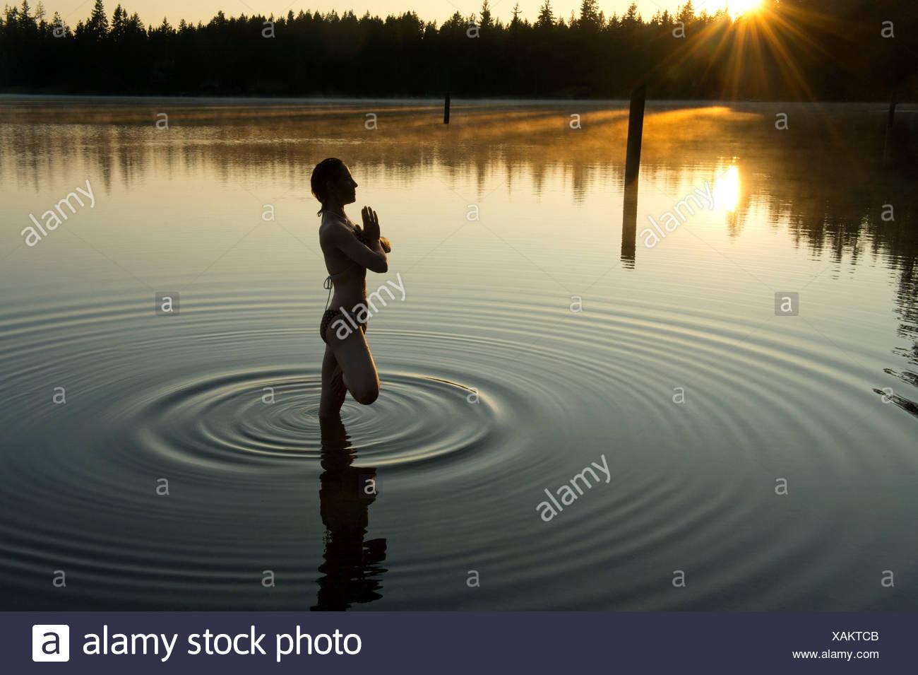Woman meditating in calm lake Stock Photo