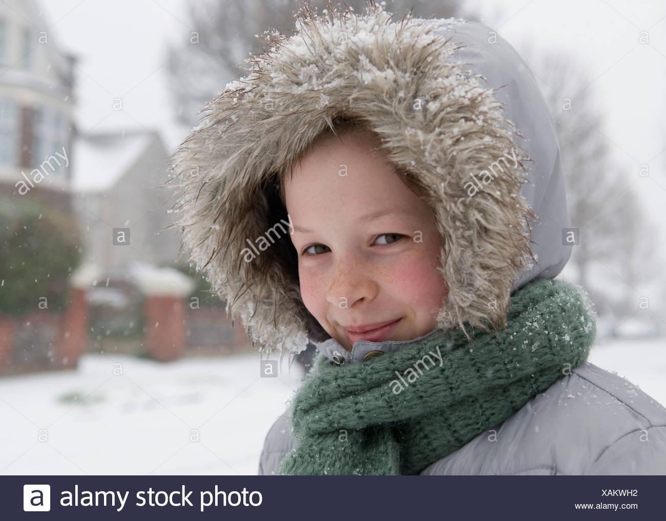 Boy wearing fur hood in snow - Stock Image