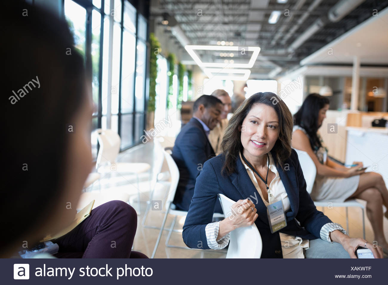 Smiling Latina businesswoman talking to colleague in conference audience - Stock Image