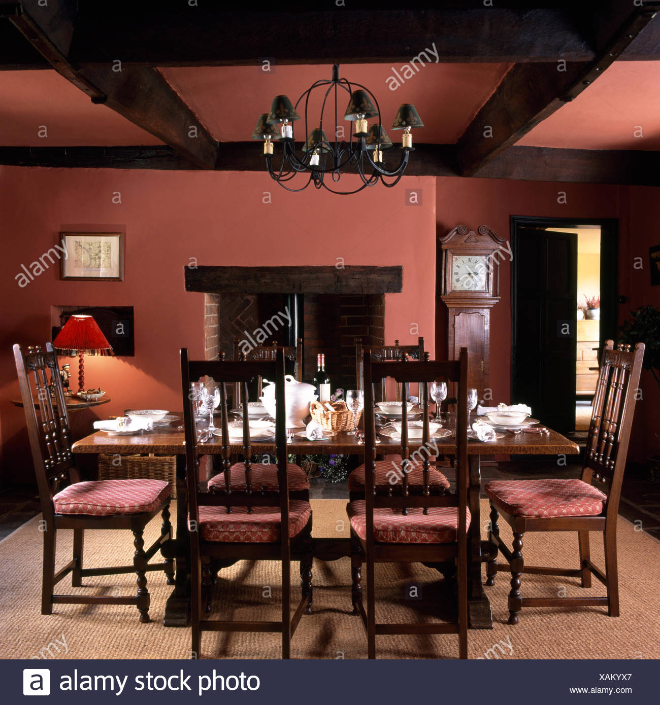 Antique Chairs At Oak Table Set For Lunch In A Deep Pink Country Dining Room Stock Photo Alamy