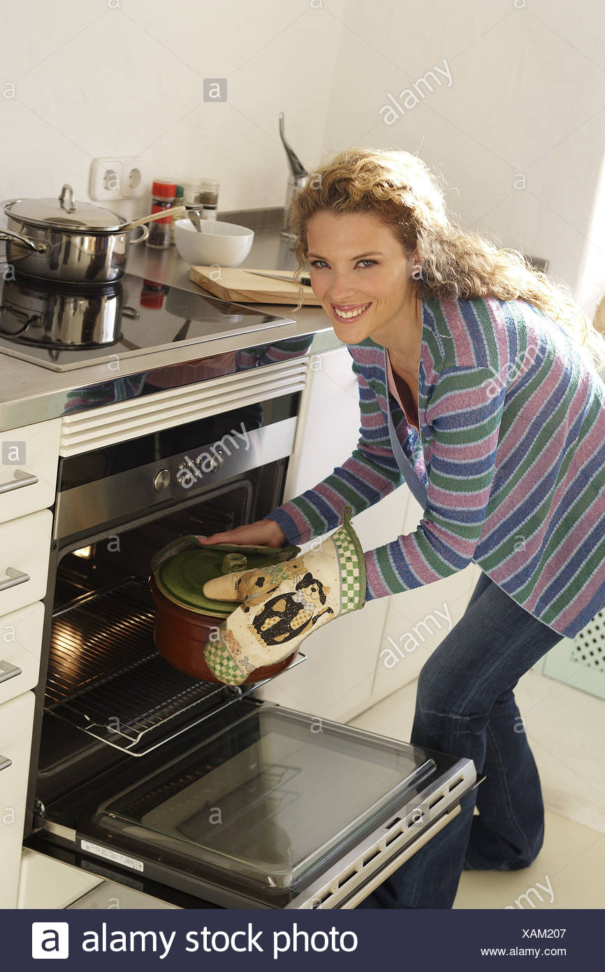 Kitchen woman pot oven takes cheerfully series people housewife hobby-cook blond laughs saucepan stewpot potholders pot-glove - Stock Image