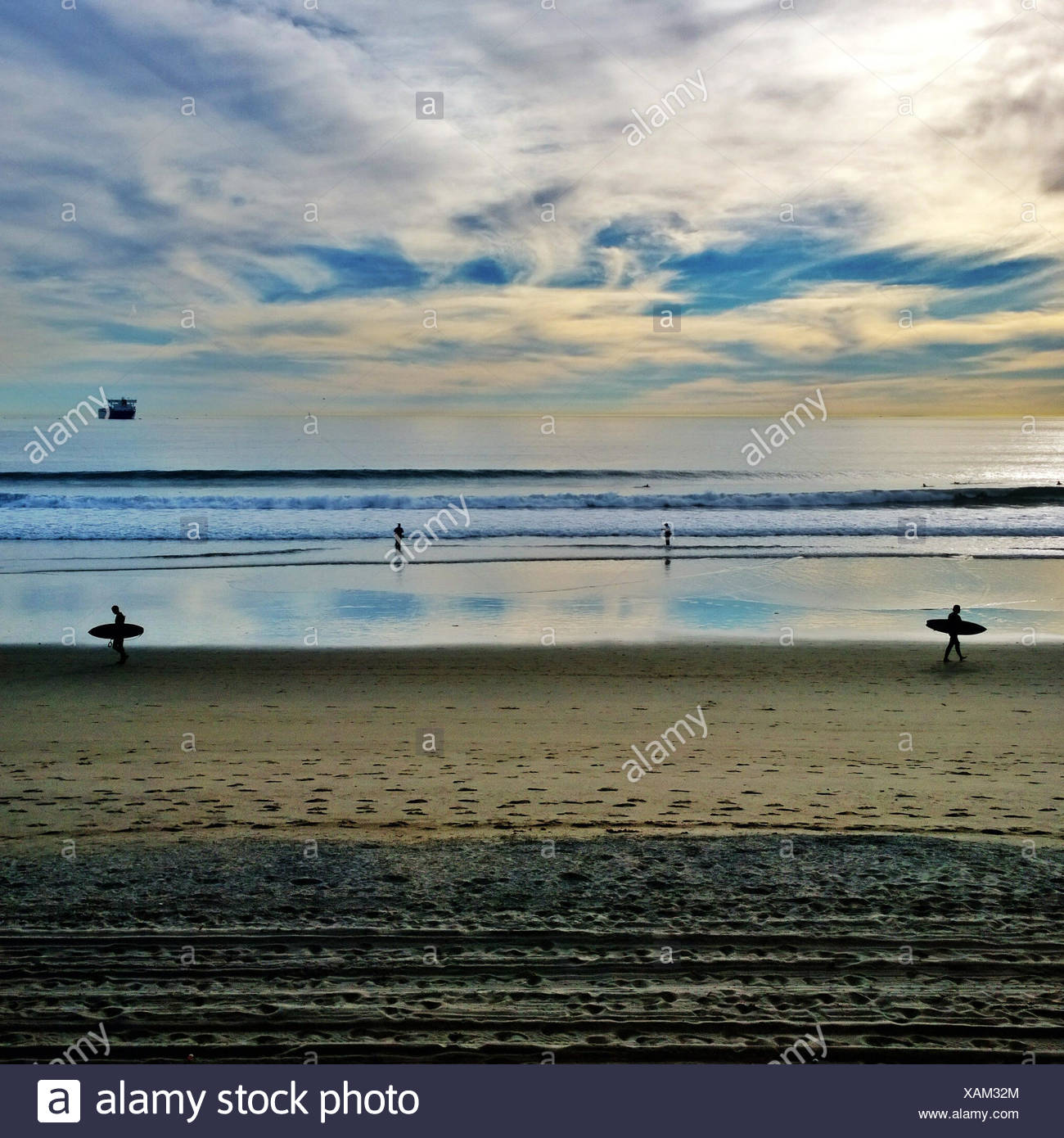 Seascape with surfers at beach - Stock Image