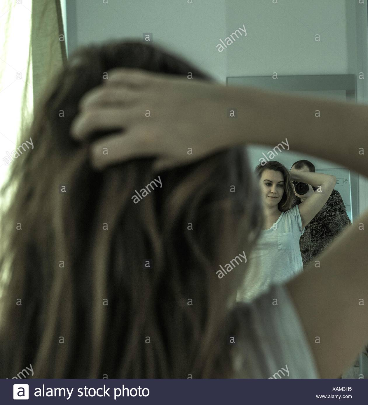 Man Photographing Woman With Hand In Hair While Reflecting On Mirror At Home - Stock Image
