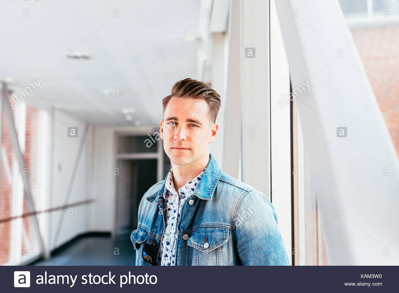 Portrait of confident media student at passage in university - Stock Image