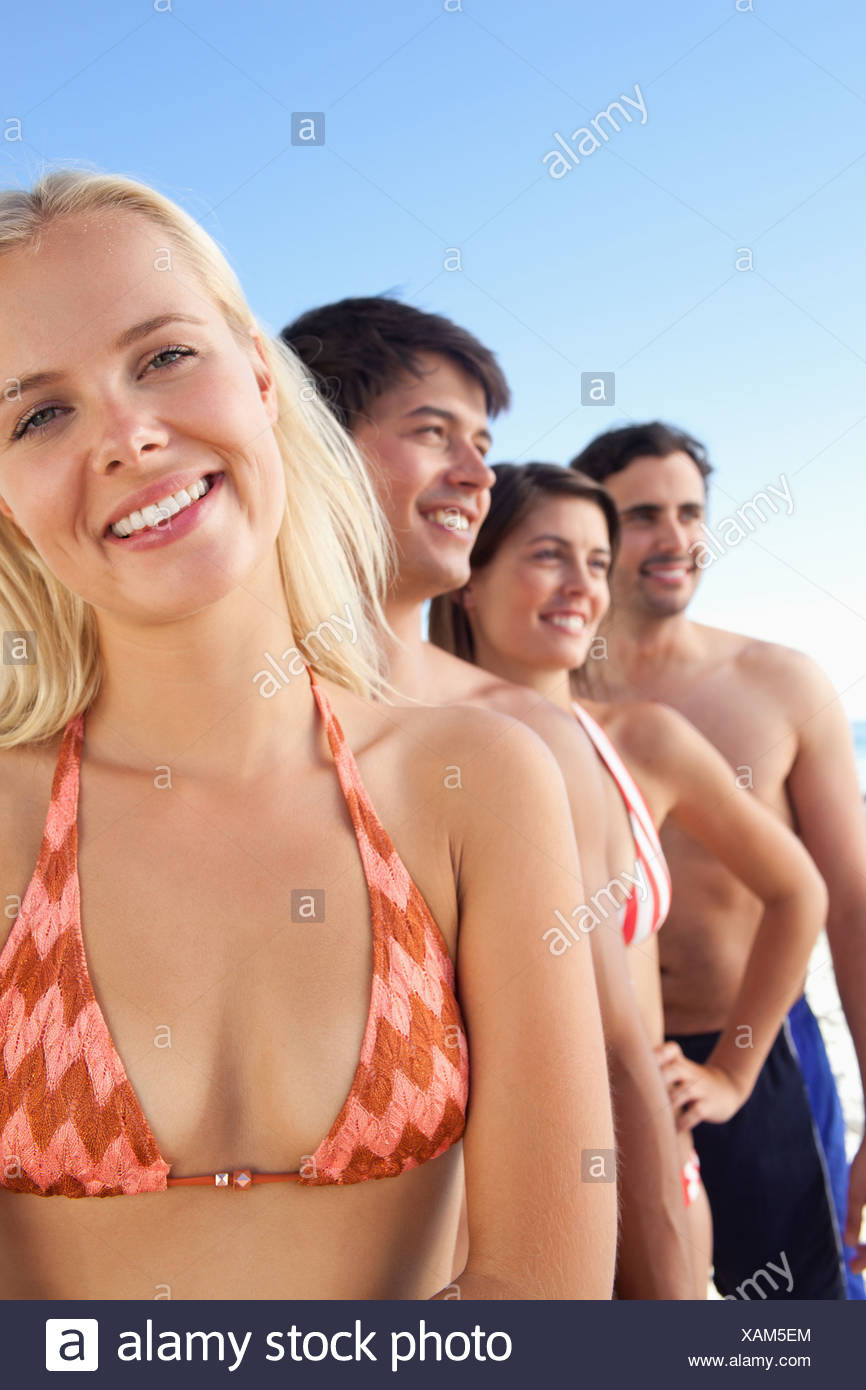 Woman smiling with her head tilted as her friends look to the side - Stock Image