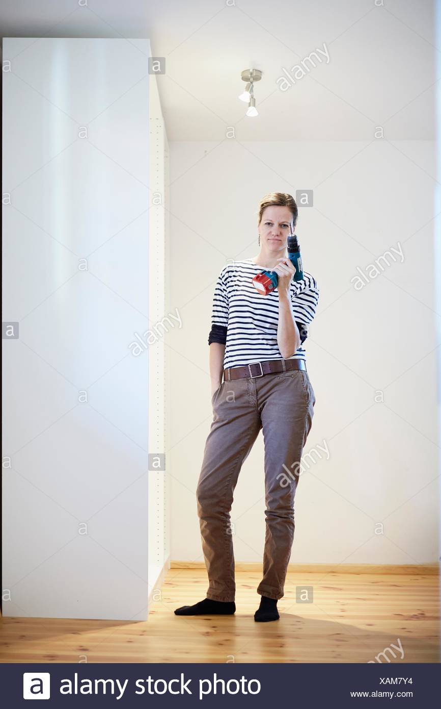 Portrait of mature woman holding up cordless screwdriver next to finished closet - Stock Image