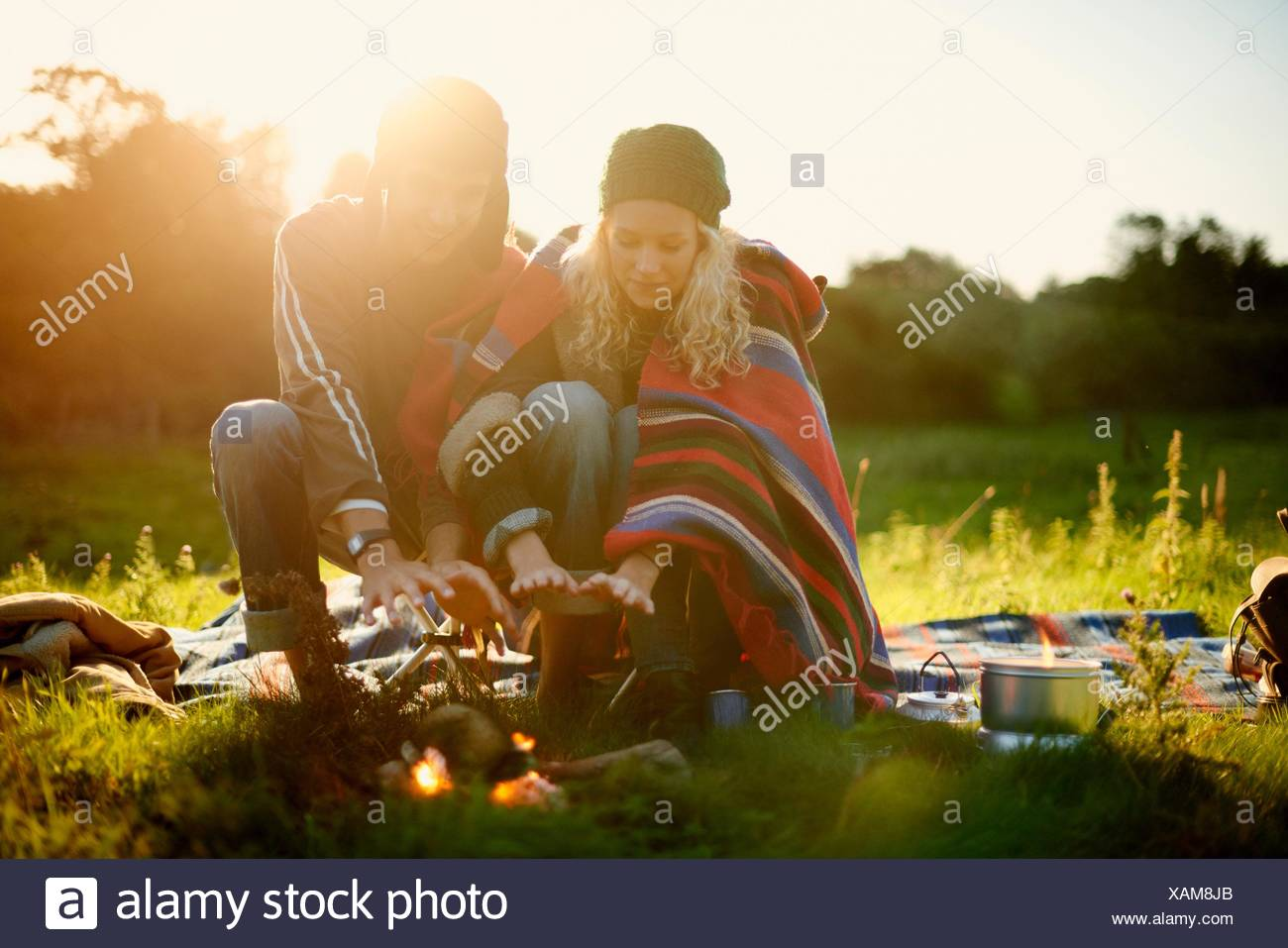 Young camping couple warming hands by campfire at dusk - Stock Image