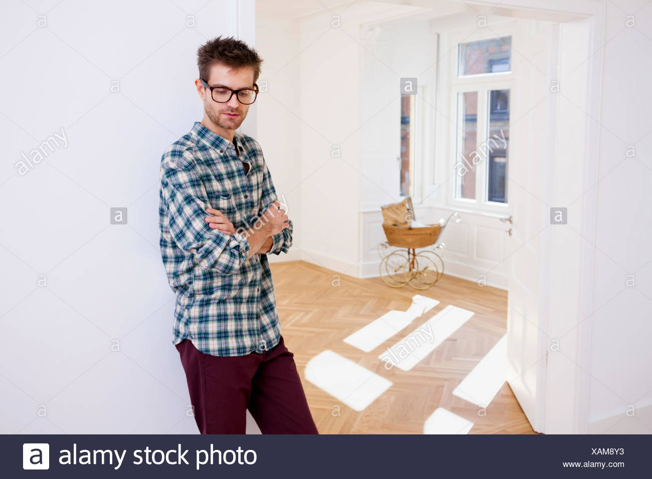 Thoughtful young man standing in new home with pram in background - Stock Image