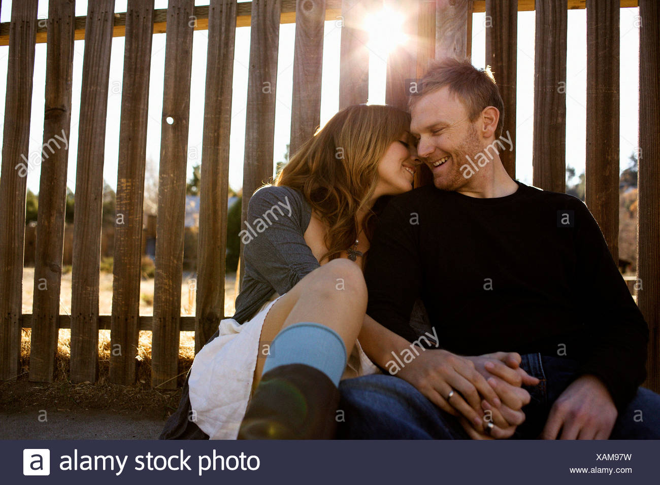 Couple sits against a fence. Stock Photo
