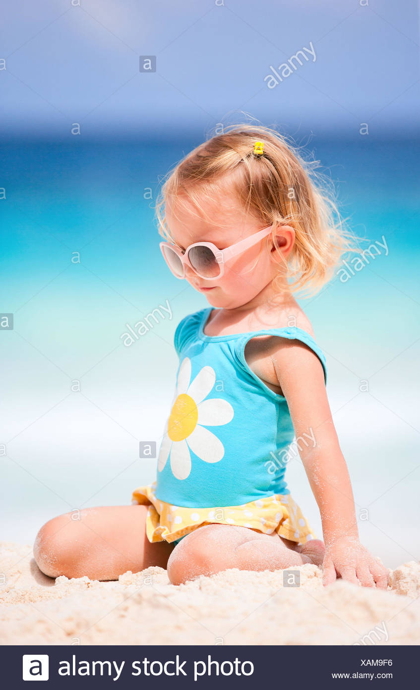 little blonde girl at tropical beach - Stock Image