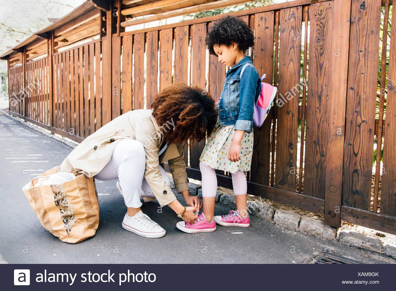 Mother kneeling by fence tying daughters shoelace - Stock Image