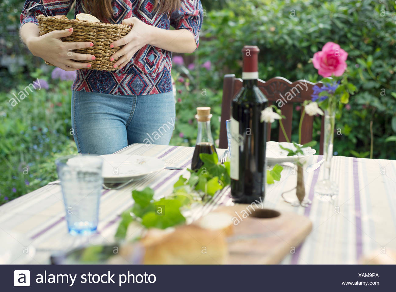 Woman setting the table outdoors - Stock Image
