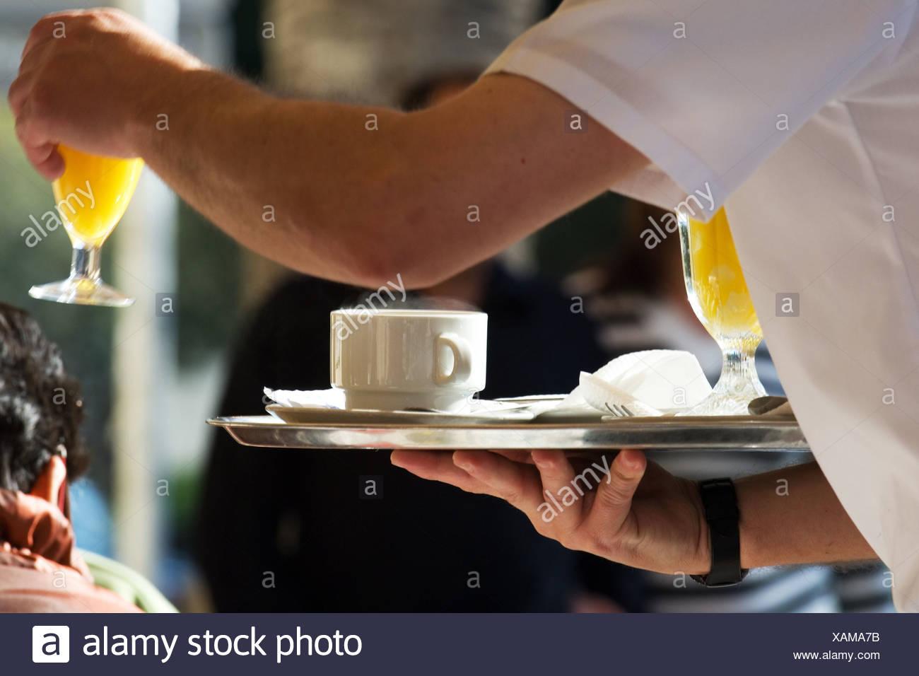 waiter serves orangejuice - Stock Image