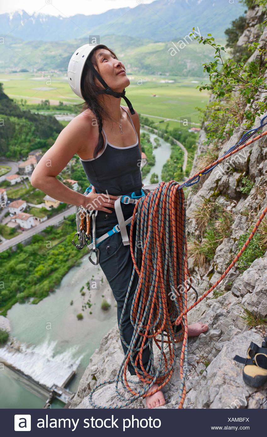 Female climber at belay point on multi pitch route, Amazziona at Piccolo Dain Parete della Centrale, Sarche, Trentino, Italy - Stock Image