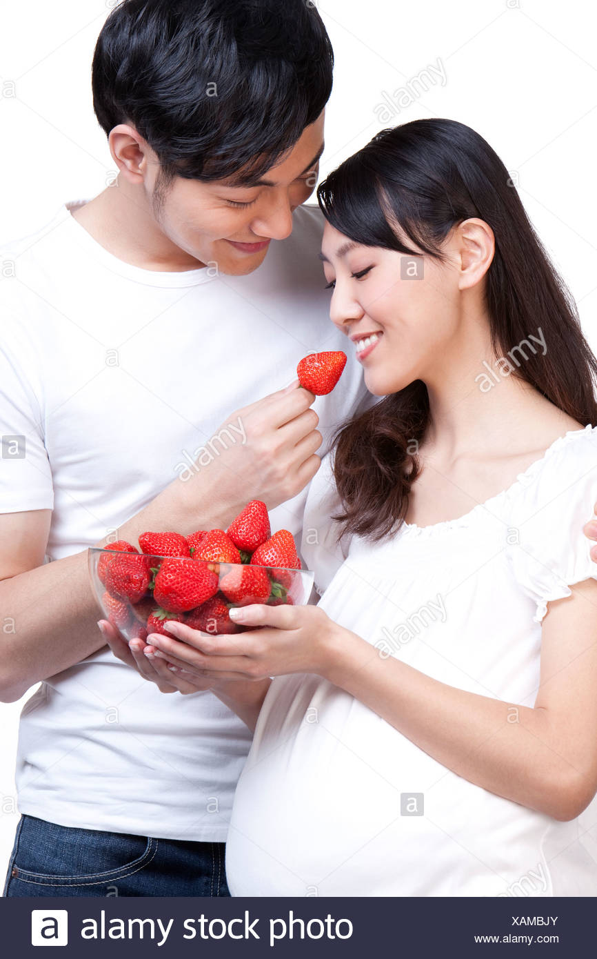 Young couple eating fresh strawberries - Stock Image