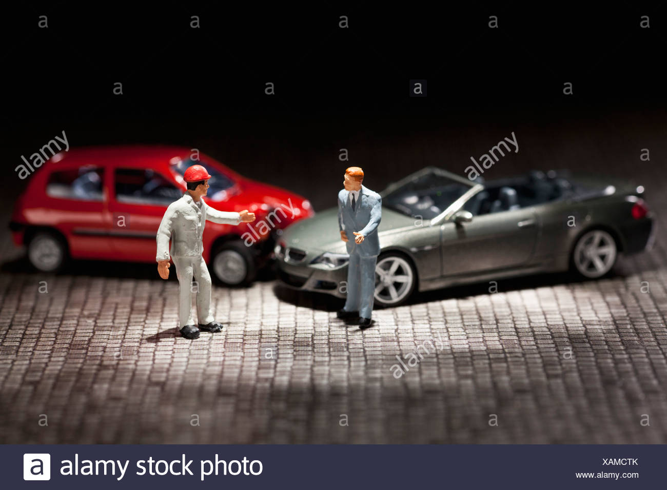 Two miniature figurine men arguing over their miniature crashed cars - Stock Image