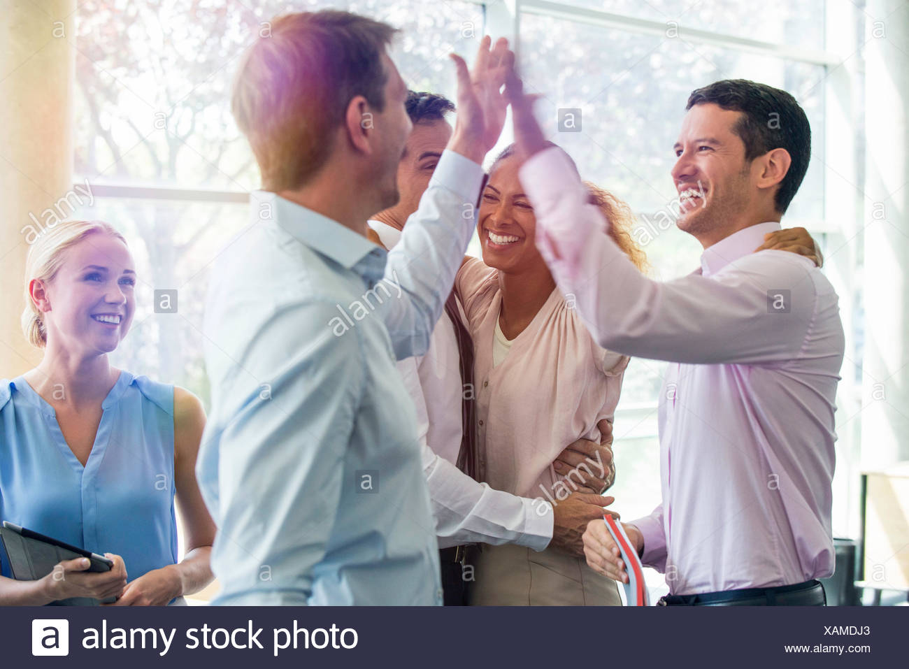 Colleagues giving each other high-five - Stock Image