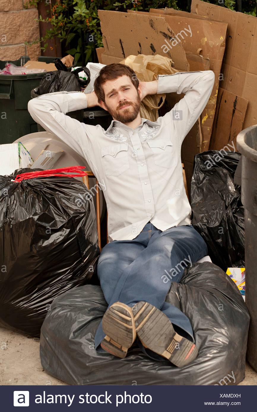 Man sitting on pile of bin bags Stock Photo