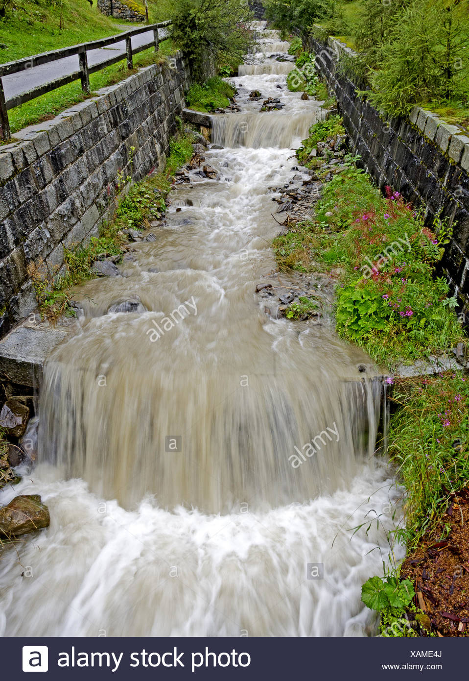 mountain torrent confined by banks - Stock Image