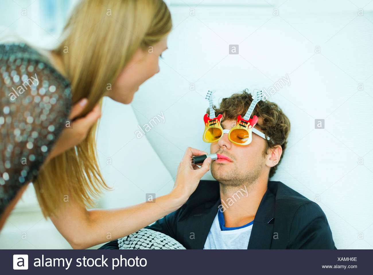 Woman applying lipstick to sleeping man at party Stock Photo