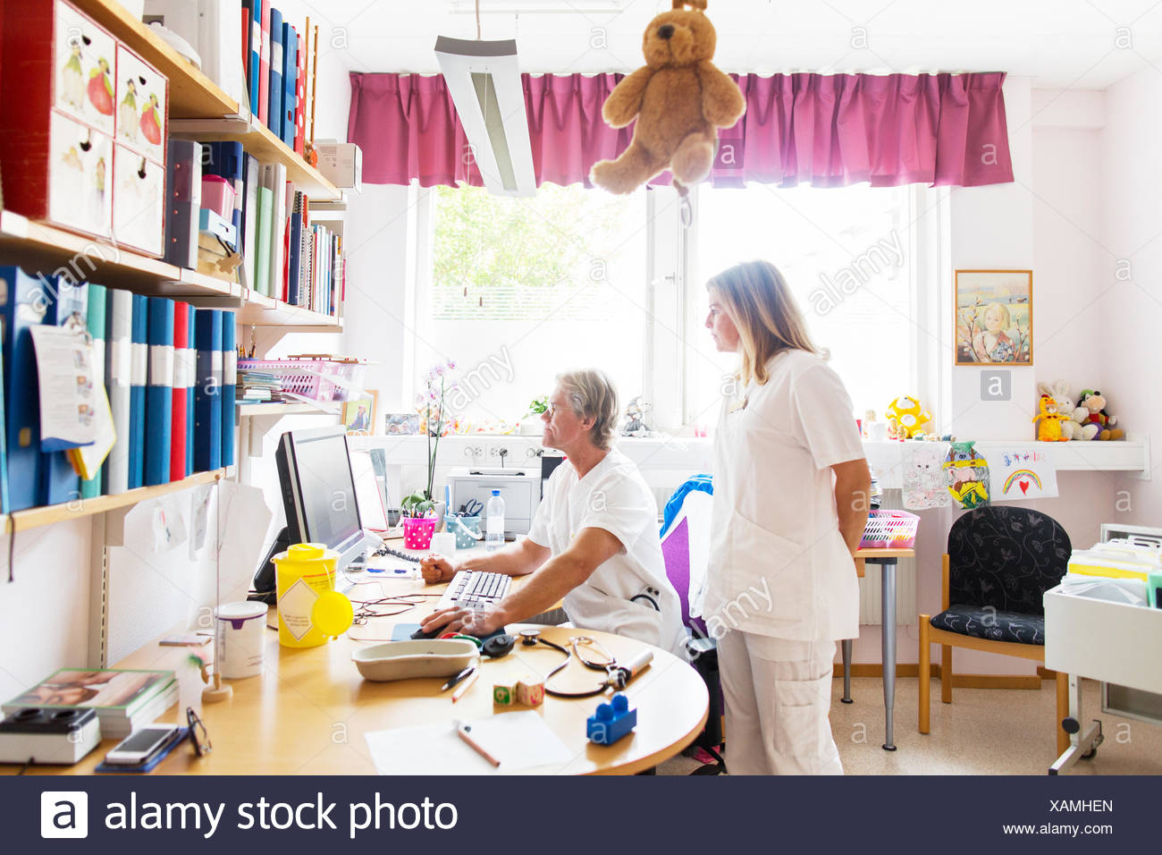 Doctor and nurse looking at computer monitor - Stock Image