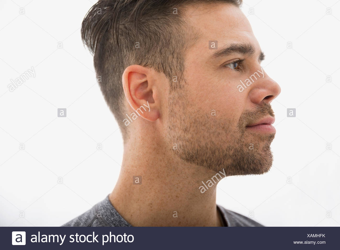 Close up of pensive brunette man looking away - Stock Image