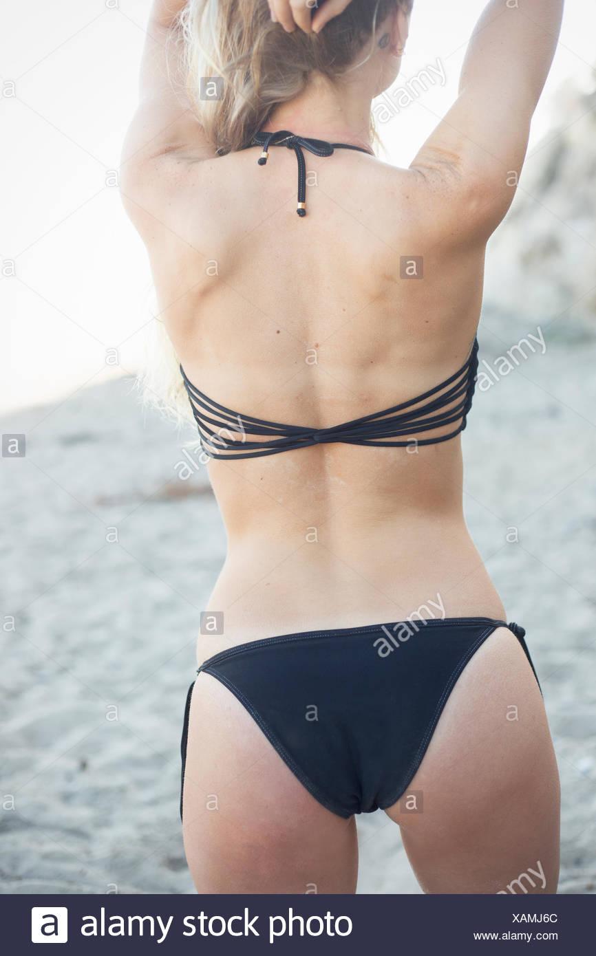 Blond woman in a black bikini on a sandy beach. - Stock Image