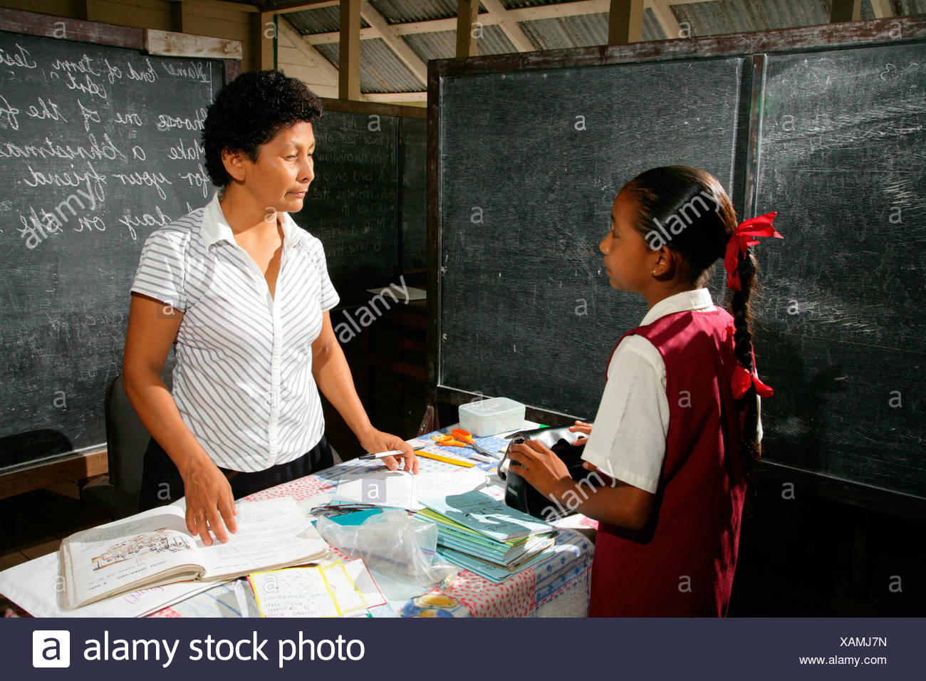 Schoolgirl and her teacher during class, Arawak natives, Santa Mission, Guyana, South America - Stock Image