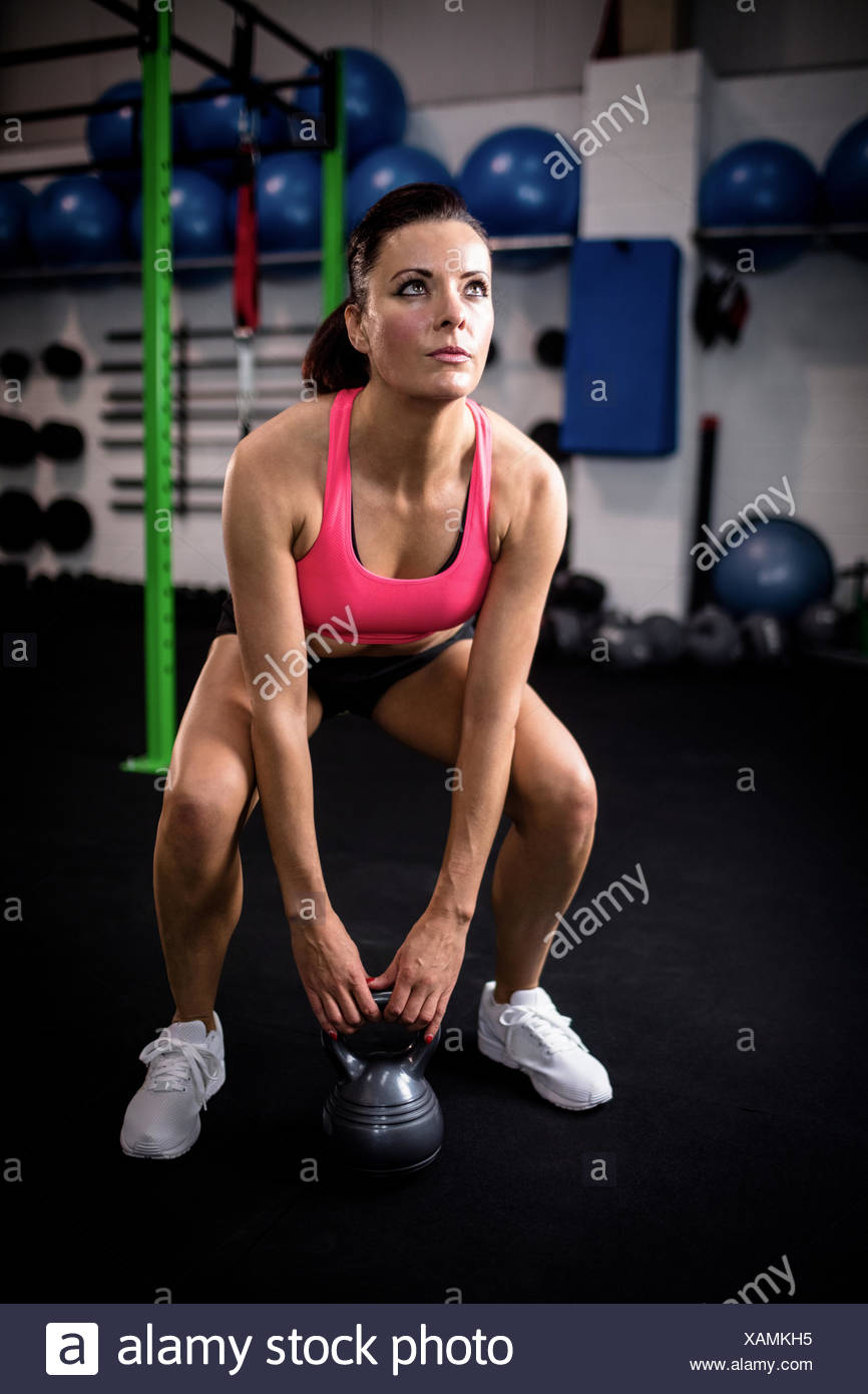 Woman exercising with kettlebell - Stock Image